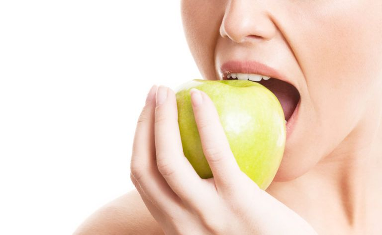 Dental Health and Your Diet - woman eating a green