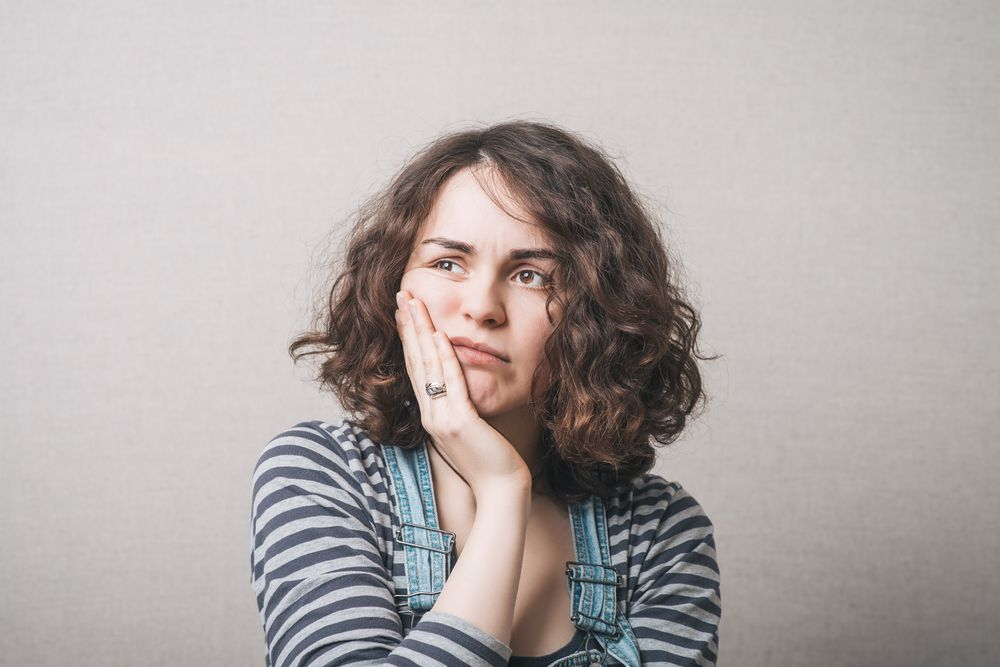 Woman toothache. Gray background unhappy