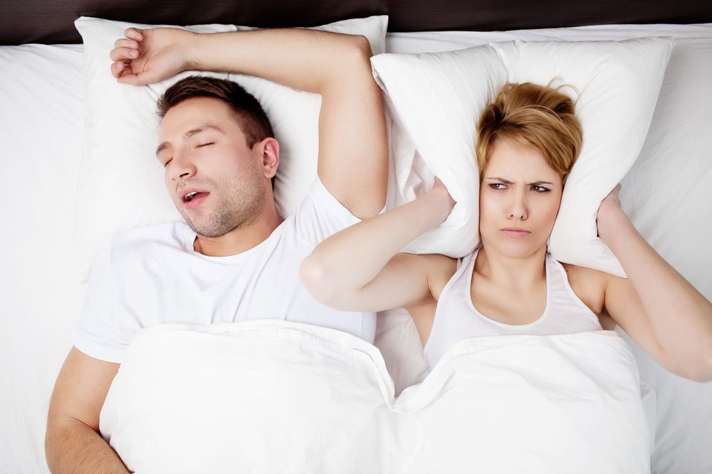 Sleep Apnea & Snoring - angry woman in bed with snoring man